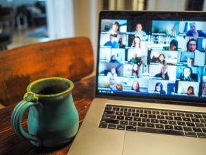 Image of a laptop screen with a video call taking place, displaying several people in small boxes on the screen. A coffee cup is to the left of the laptop.